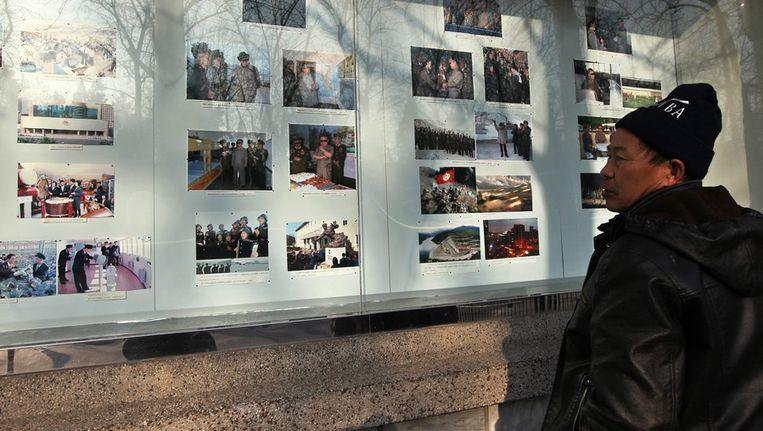 Een man bekijkt foto's van Kim Jong-il bij de Noord-Koreaanse ambassade in Peking. Beeld epa