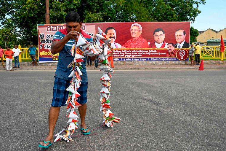 Een aanhanger van de partij van Rajapaksa legt een lint vuurwerk klaar om de overwinning te vieren. Beeld AFP