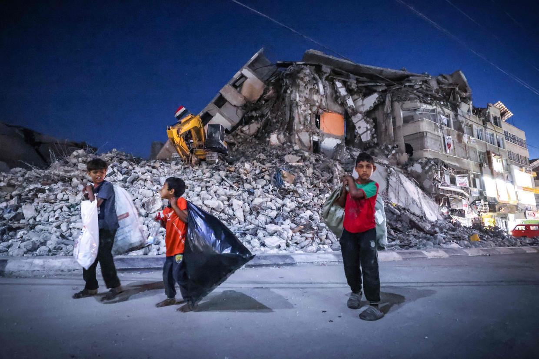 Palestijnse jongens lopen langs een door Israël verwoest gebouw in Gaza Stad.