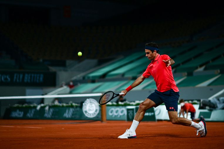 Roger Federer retourneert de bal in een donker en leeg Court Philippe Chatrier, in Parijs. Voor de achtste finale van Roland Garros geeft hij forfait. Beeld AFP