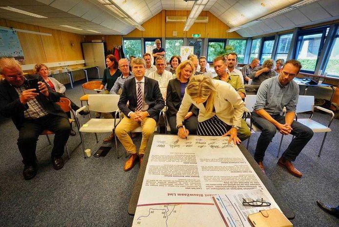 Anneke Kool van de provincie Utrecht zet haar handtekening. Achter haar kijken Michiel Houtzagers (Zuid-Hollands Landschap), wethouder Christa Hendriksen (Vijfheerenlanden), René Garskamp (Utrechts Landschap) en Max Zevenbergen (Natuur- en Milieu Federatie Utrecht) toe.