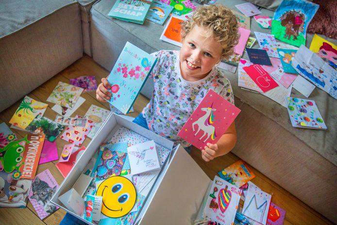 Maeve met alle kaartjes die ze kreeg toen ze in het ziekenhuis lag en voor altijd bewaarde.