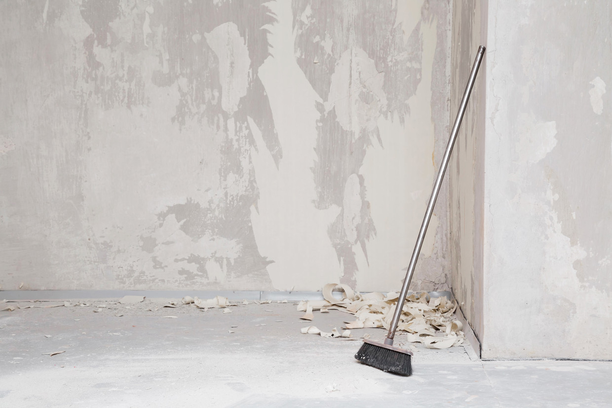Broom at wall in room. Sweeping white concrete dust and old wallpaper from floor. Cleaning garbage after repair work of home. Front view.