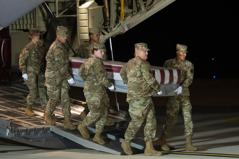 Een team van de Amerikaanse luchtmacht draagt de kist van een militair die werd neergeschoten op de luchtmachtbasis in Florida. Beeld AP | Associated Press
