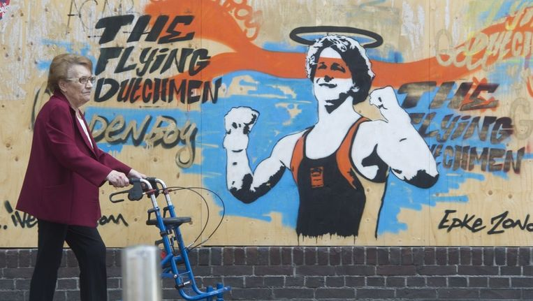 Een oude dame passeert een muurschildering van turner Epke Zonderland. Kunstenaar Ives One heeft een hommage aan de sportheld aangebracht op een dichtgespijkerd pand in Amsterdam-oost. Beeld anp