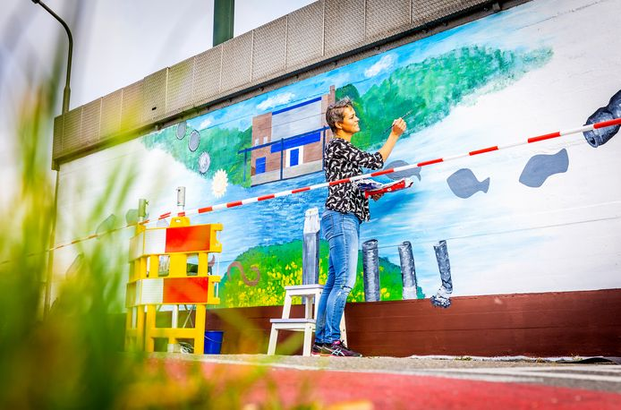 Het kunstwerk op de muur van gemaal De Eendragt. Ida Wiersma legt er de laatste hand aan.