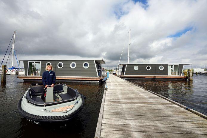 Bij Jachthaven de Waterkant kun je boothuisjes en sloepen huren. Havenmeester Macy van Sabben in een van de sloepen, op de achtergrond de boothuisjes.