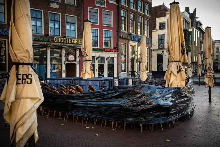 De tafels en stoelen op de terrassen op de Grote Markt in Groningen zijn opgestapeld en opgeruimd.  Beeld Kees van de Veen