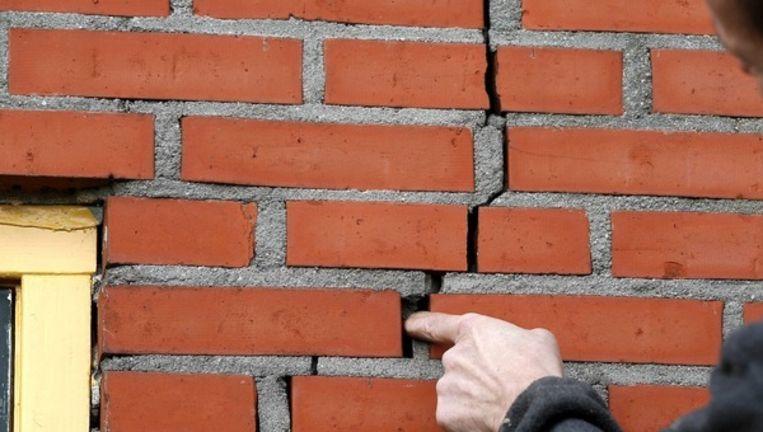 Een man in het Groningse gehucht Doodstil stelt de schade aan zijn huis vast na twee bevingen in dezelfde nacht. Archieffoto uit februari 2013.