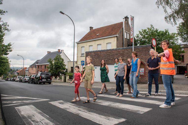 Schooldirecteur Evelien Gauquier (met bordje), haar schoolteam en leden van de partij Groen vinden dat de stad sneller werk moet maken van de verbetering van de verkeersveiligheid aan de KBO-school in Volkegem.