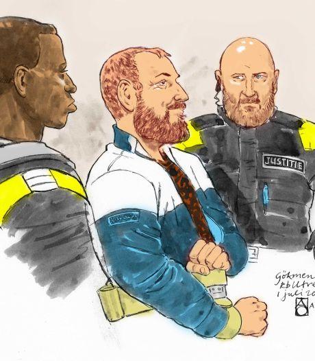 Met een brutale blik en spottend lachje loopt Gökmen Tanis de rechtszaal in