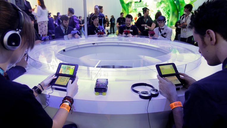 Gamers spelen op de E3 2013 met een Nintendo 3DS. (Archieffoto) Beeld AP