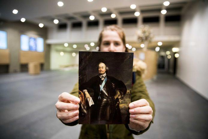 Een medewerker van het Mauritshuis toont een portret van Johan Maurits op de plek in de foyer waar tot afgelopen zomer zijn borstbeeld stond. Dat ligt nu in het depot.