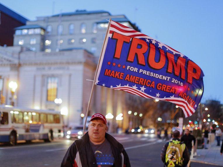 Trump-aanhanger Philip Farren zwaait met een vlag woensdag in Washington. Verwacht wordt dat honderdduizenden tegenstanders van Trump vrijdag tegen zijn beëdigen zullen protesteren.  Beeld EPA