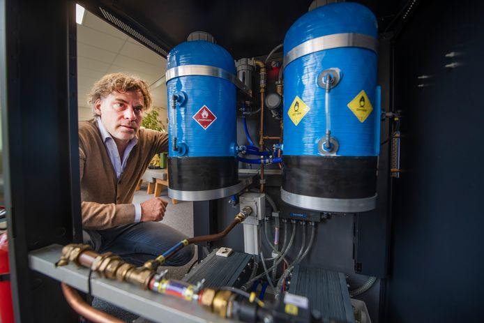 Wilko van Kampen is directeur van XINTCglobal, een bedrijf dat elektrolysers gaat maken. Dat zijn een soort waterstoffabrieken. Op de foto knielt hij bij een demo-model.