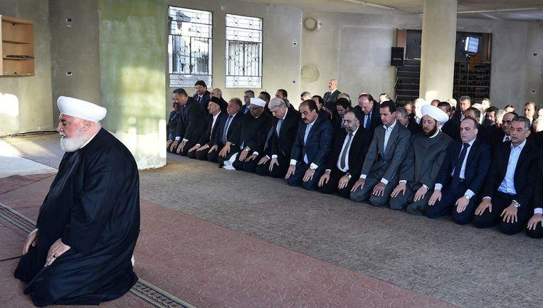 Assad (vierde van rechts) bidt tijdens Eid al-Adha in een moskee in Darayya. Beeld afp