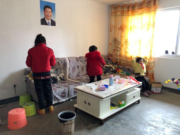 Aniu's gezin in hun nieuwe appartement in de stad, met het portret van president Xi aan de muur. Beeld Leen Vervaeke