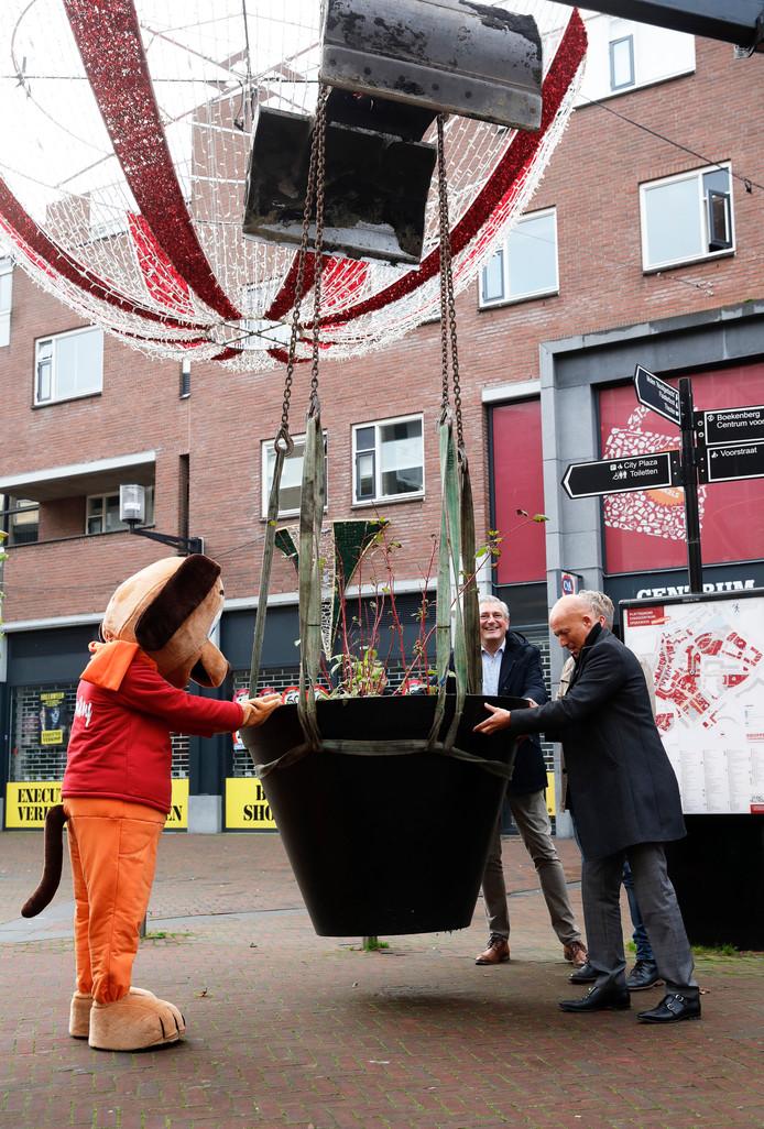 De enorme plantenpot wordt met een kraan en met hulp van Ad Dekkers (achter), wethouder Mijnans (r), de bijna niet zichtbare wethouder Soeterboek en mascotte Spikey op zijn plaats gezet in het centrum van Spijkenisse.