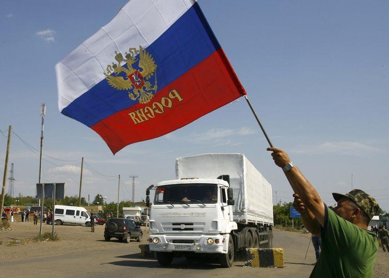 Een buurtbewoner zwaait met de Russische vlag terwijl een aantal vrachtwagens uit het Russische hulpkonvooi de grens met Oekraïne oversteken. Beeld afp