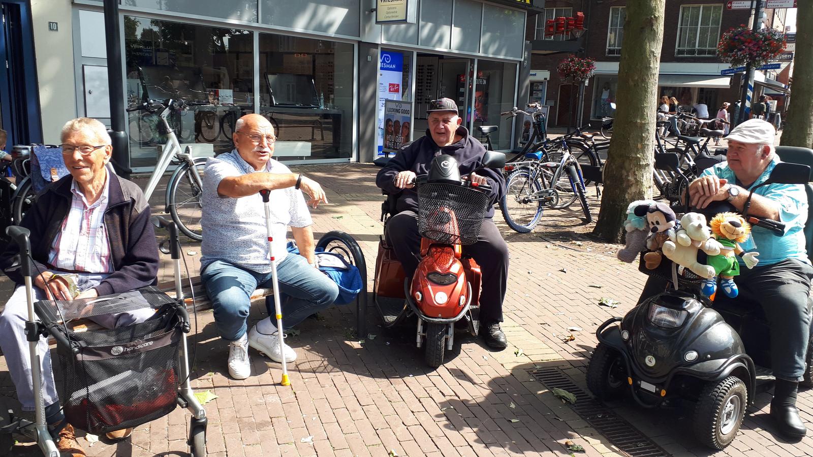 Berry van Rijnsoever, Jan Nas, Geert Bolder en Henk Kelderman (vlnr) bij 'hun' bankje aan het Raadhuisplein in Zevenaar.