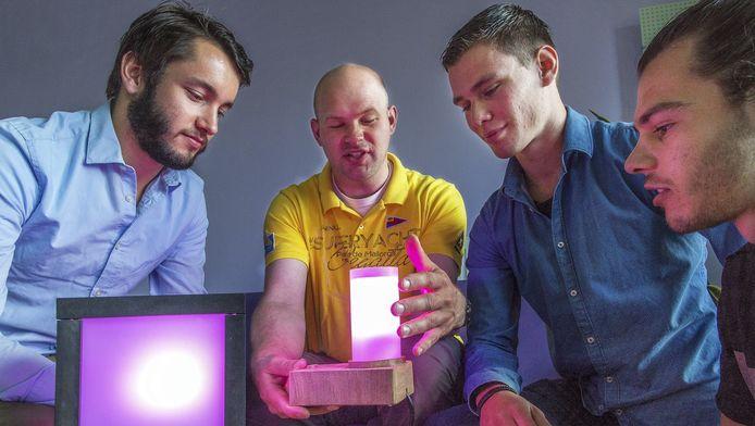 Cliënt Alex van Ravenswaay Claasen Houdt de speciale lamp omhoog. De studenten Dion Koppers (l), Malte ten Wolde en Milan van der Gronde kijken tevreden toe.