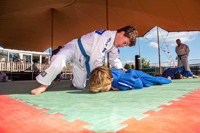 Trainer Ed van de Berg geeft weer training aan de jongste jeugd bij Theo Meijer. In de buitenlucht, onder een afdak.