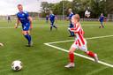 De kleintjes en de oudjes speelden als eerste op het nieuwe veld. Seban Wingens was de veteranen, onder wie zijn opa, te snel af.