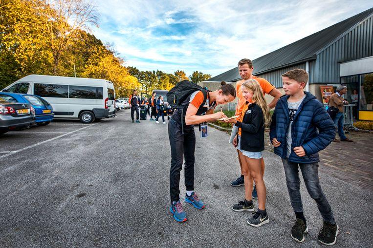 Marjolijn Kroon deelt een handtekening uit wanneer het Nederlands team aankomt bij de sporthal. Beeld Raymond Rutting / de Volkskrant