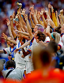 De Nederlandse voetbalvrouwen kijken toe hoe de Amerikanen feest vieren.