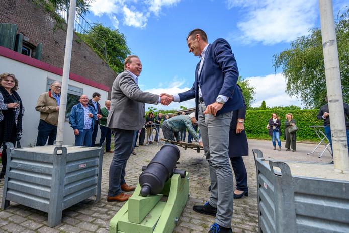 Het kanon van Fort Sabina is overhandigd. Wethouder Thomas Zwiers (links) schudt de hand van zijn collega Daan Markwat van de gemeente Goeree-Overflakkee, op Fort Prins Frederik in Ooltgensplaat.