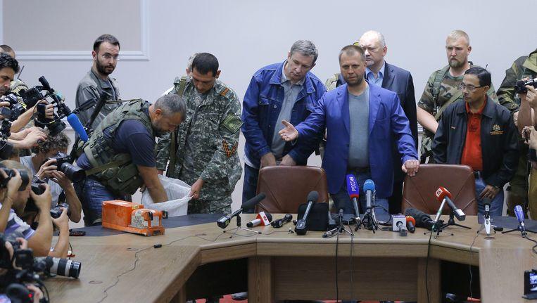 'Premier' Aleksandr Borodaj (M) van de zelfuitgeroepen Volksrepubliek Donetsk draagt de zwarte dozen van het rampvliegtuig MH17 van Malaysia Airlines op 22 juli over aan een Maleisische delegatie. Beeld EPA