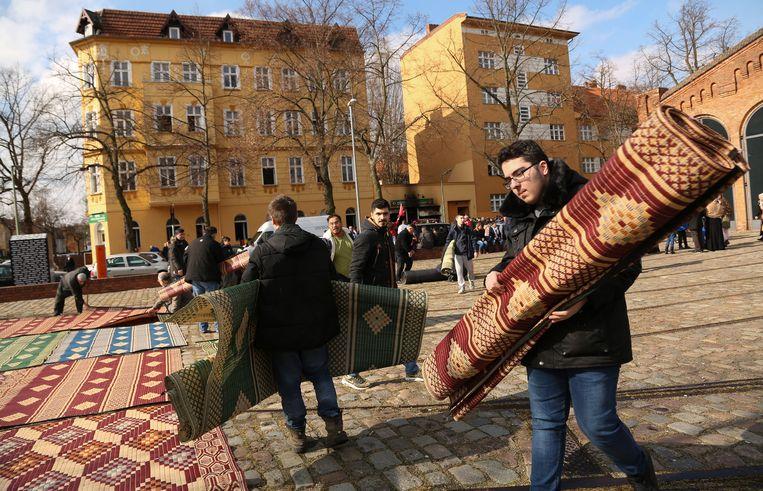 Bezoekers van de Koca Sinan Camii in Berlijn leggen hun bidkleed buiten neer, nadat hun moskee door brandbommen deels is verwoest. Beeld Getty Images