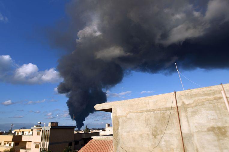 Rook stijgt op uit de haven van Benghazi. Archiefbeeld uit 20014. Bij een ontploffing van een bomauto in de Libische havenstad Benghazi zijn deze nacht zeker zeven mensen omgekomen. Minstens 22 andere mensen raakten gewond. Beeld AFP