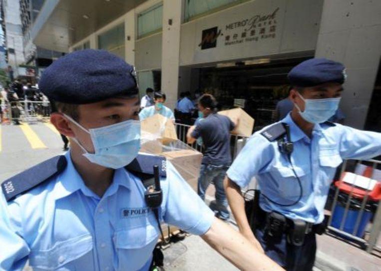 Politieagenten met mondkapjes bewaken de in- en uitgangen van het hotel Metropark in de wijk Wanchai, Hong Kong. ANP Beeld