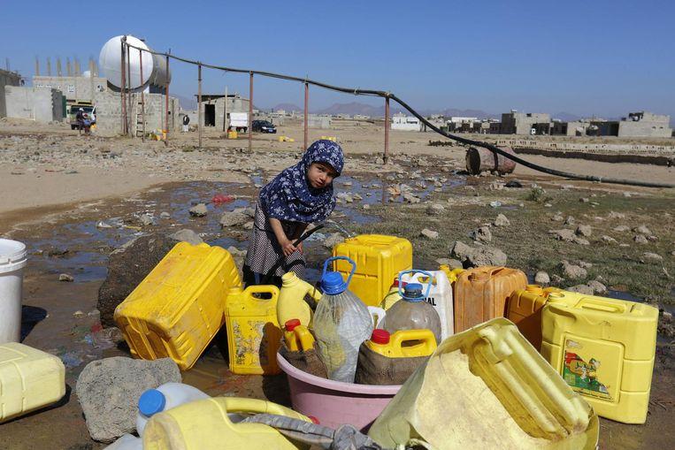Een meisje vult in de hoofdstad Sanaa jerrycans met water. Het overgrote deel van de 24 miljoen inwoners van Jemen is het slachtoffer geworden van de ineenstorting van openbare voorzieningen door de oorlog. Beeld EPA