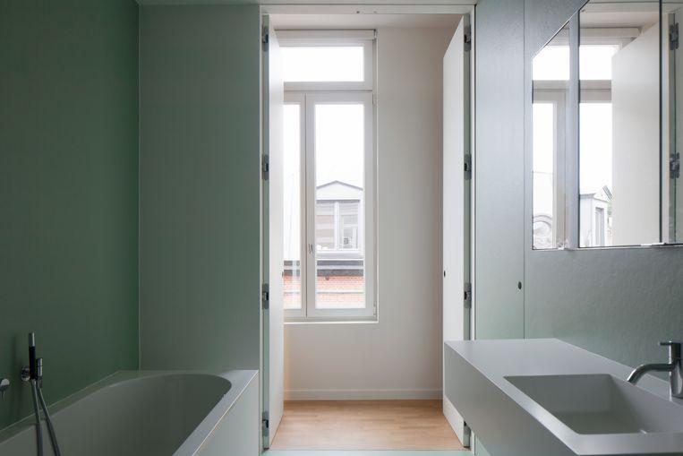 De badkamer van groene polyester zit in een apart volume. Ook hier is de opbergruimte verstopt achter een geheime wand.  Beeld Johnny Umans