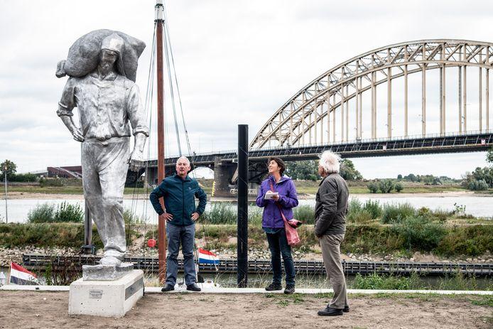 Kunstkenners Frank van de Schoor (links) en Daan van Speybroek (rechts) bekijken samen met Gelderlanderjournalist Anne Nijtmans (midden) De Kaaisjouwer