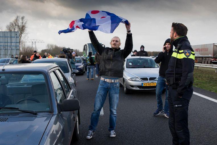 Twee bussen van de actiegroep Stop Blackface worden door tegendemonstranten tegengehouden op de A7 bij Joure. Beeld anp