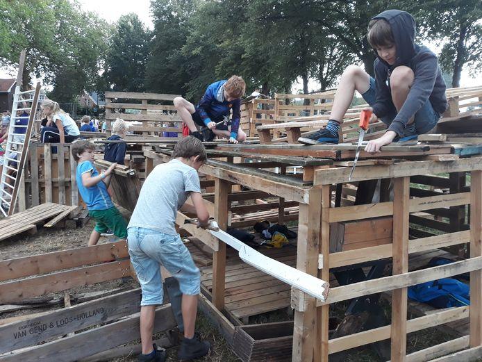Boris, Joris, Micah en Jop werken flink door om bij Mini-Gestel hun hut van een dicht dak te voorzien, 2018.