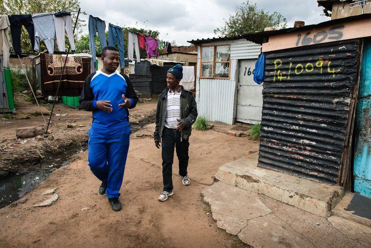 Sithembiso Yingwane (links) en Elias Mokhabi wandelen door een steeg in de sloppenwijk Freedom Charter in het Zuid-Afrikaanse township Soweto. Beeld Bram Lammers