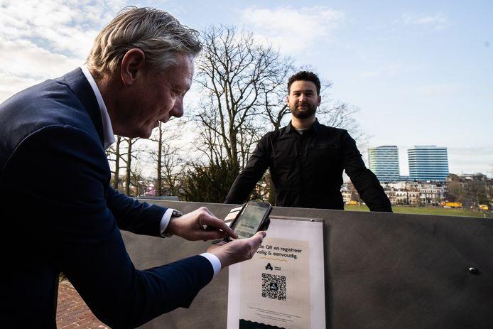 Wethouder Economische Zaken Jan van Dellen scoort zijn QR-code voor toelating bij Matthijs Holtackers van Stadsvilla Sonsbeek.