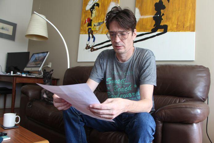 Joop Simons thuis op de bank met een brief uit de jarenlange correspondentie met Sociale Dienst Oost Achterhoek.