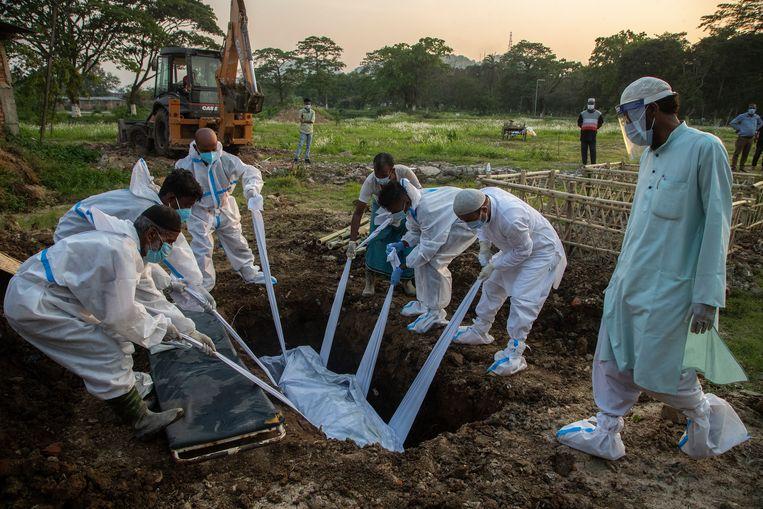 India is hard geraakt door de coronacrisis. Familieleden begraven een overleden coronapatiënt in Gauhati. Beeld AP