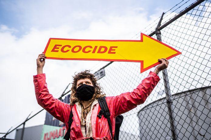 Actievoerder toont een protestbord in de bedrijfskleur van Shell bij de opslag voor olie in Arnhem.