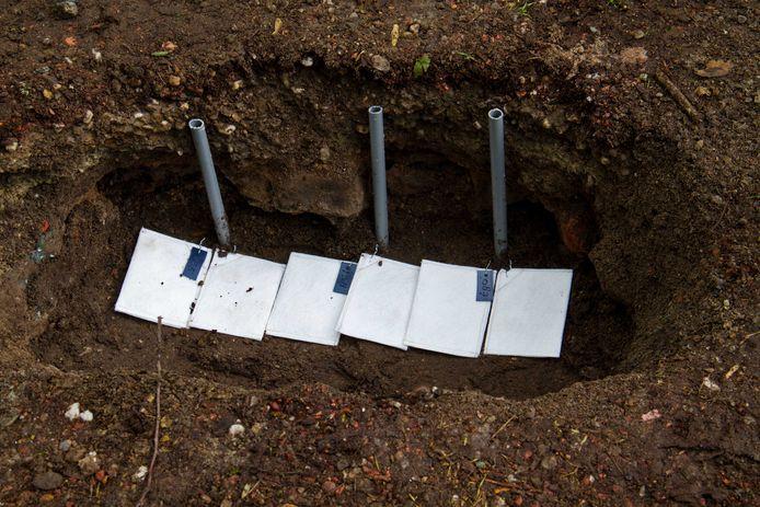 Zakjes met asbestvezels, die voor het onderzoek onder de grond begraven werden.