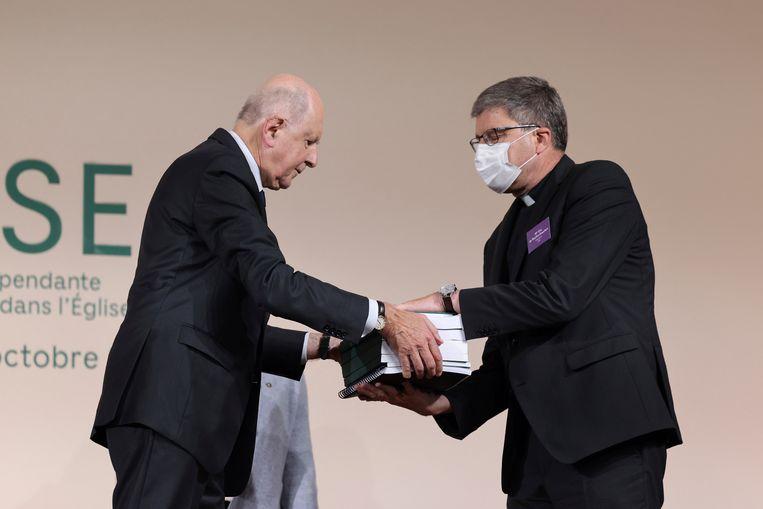 Commissievoorzitter Jean-Marc Sauvé (links) overhandigt exemplaren van het misbruikrapport aan Eric de Moulins-Beaufort, voorzitter van de Bisschoppenconferentie van Frankrijk (CEF). Beeld AP