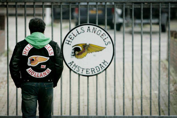 Een lid van de Amsterdamse afdeling van de Hells Angels bij het clubhuis. Het Openbaar Ministerie (OM) gaat proberen alle Nederlandse afdelingen van de Hells Angels te verbieden.
