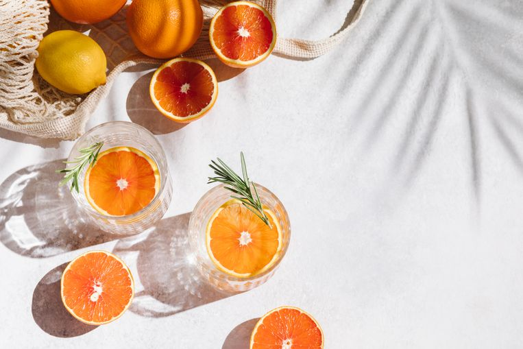 Summer orange cocktails with fresh citrus fruits. Hard seltzer, lemonade, refreshing drinks, low alcohol mocktails, summer party concept. Trendy shadow and sunlight. Flat lay, top view, copy space Beeld Getty Images/iStockphoto