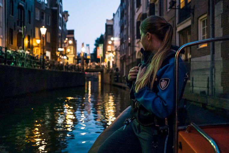 Handhaver Jody (22) patrouilleert op een boot in de grachten. Beeld Marcel Wogram