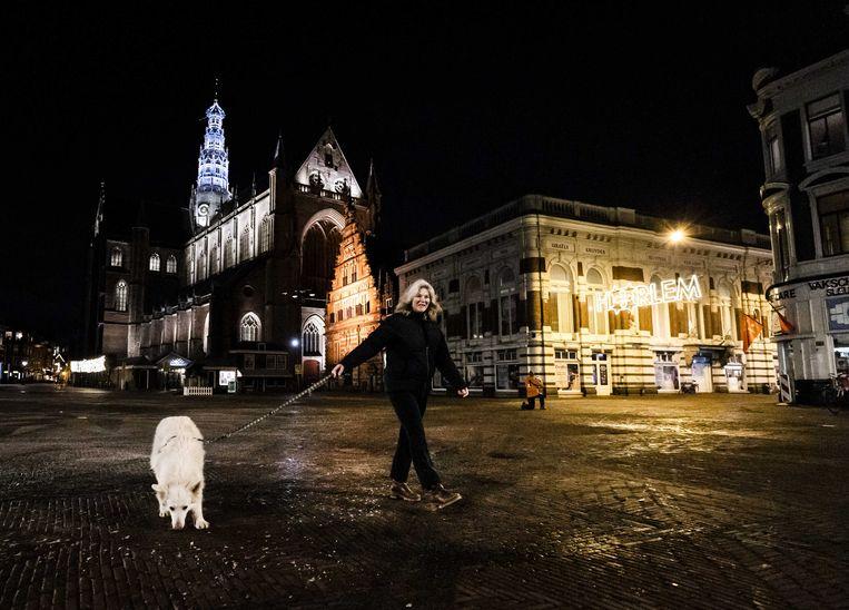 Een vrouw in Haarlem laat haar hond uit tijdens de avondklok. Beeld ANP